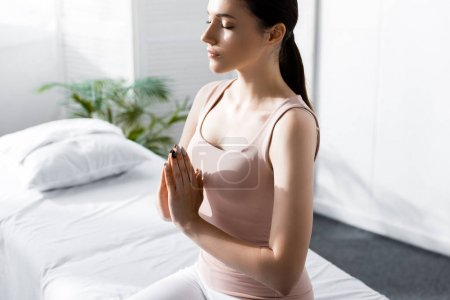 Photo for Woman sitting on massage table with closed eyes and showing namaste sign in clinic - Royalty Free Image
