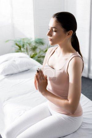 Photo pour Femme assise sur une table de massage les yeux fermés et montrant un signe namaste à la clinique - image libre de droit