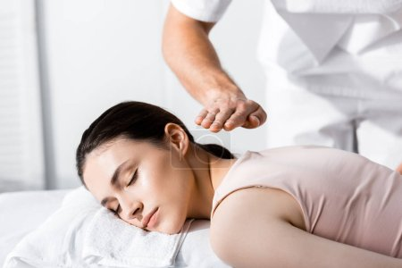 Photo for Cropped view of healer standing near woman lying with closed eyes on massage table and holding hands above her body - Royalty Free Image