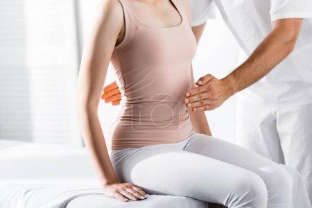 Photo pour Vue recadrée de la femme assise sur une table de massage pendant que le guérisseur nettoie son aura - image libre de droit