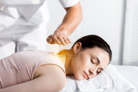 Foto de Vista recortada del sanador de pie cerca de la mujer acostada con los ojos cerrados y sosteniendo las manos por encima de su cuerpo - Imagen libre de derechos