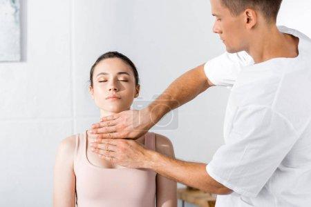Photo pour Femme s'asseyant avec les yeux fermés tandis que le guérisseur nettoyant son aura - image libre de droit