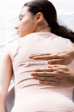Foto de Vista recortada del sanador de pie cerca de la mujer acostada con los ojos cerrados y sosteniendo las manos sobre su cuerpo - Imagen libre de derechos