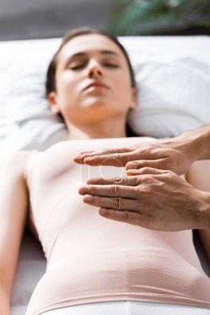 Photo pour Vue recadrée du guérisseur debout près d'une femme couchée les yeux fermés et tenant les mains au-dessus de son corps - image libre de droit