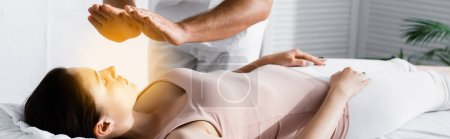 Photo for Panoramic shot of cropped view of healer standing near woman on massage table and cleaning her aura - Royalty Free Image