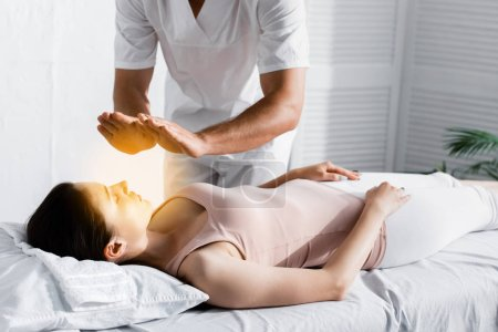 Photo for Cropped view of healer standing near woman on massage table and cleaning her aura - Royalty Free Image