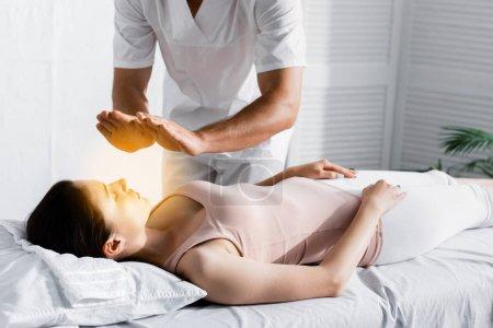 Photo pour Vue recadrée du guérisseur restant près de la femme sur la table de massage et nettoyant son aura - image libre de droit