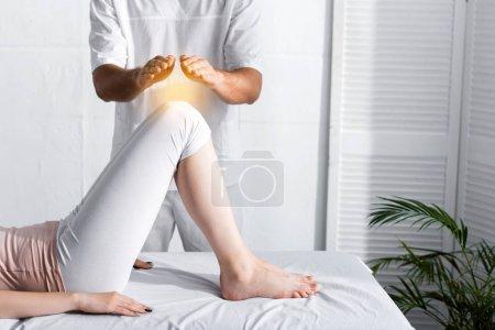 Foto de Vista parcial del sanador de pie cerca de la mujer en la mesa de masaje y tomar las manos por encima de sus rodillas - Imagen libre de derechos