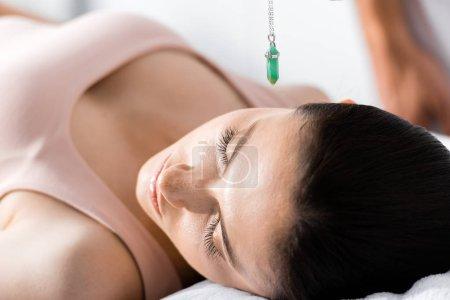 Photo pour Femme avec les yeux fermés et la pierre verte au-dessus de sa tête - image libre de droit
