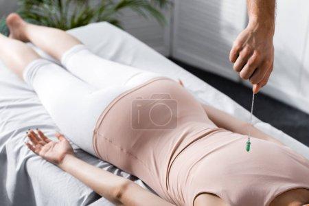 Photo pour Vue recadrée de l'hypnotiseur restant près de la femme sur la table de massage et retenant la pierre verte - image libre de droit