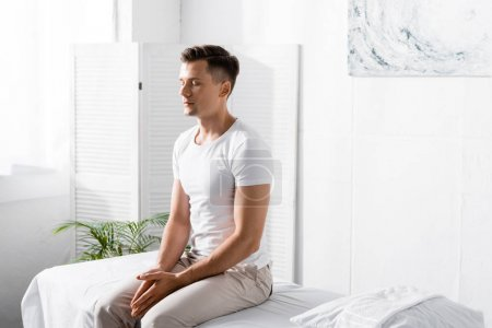 Photo pour Homme dans le t-shirt blanc s'asseyant sur la table de massage avec les yeux fermés dans la clinique - image libre de droit