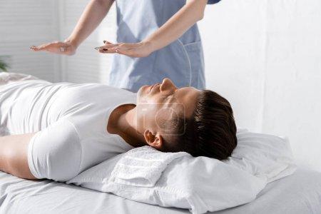 Photo pour Vue partielle du guérisseur restant près de l'homme sur la table de massage et retenant des mains au-dessus de son corps - image libre de droit