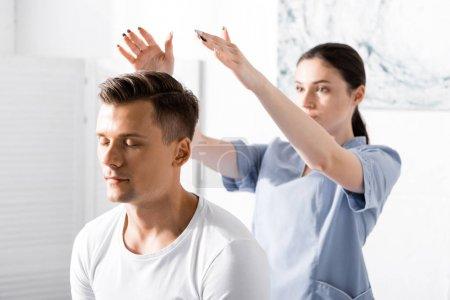 Photo pour Homme s'asseyant avec les yeux fermés tandis que le guérisseur nettoyant son aura - image libre de droit