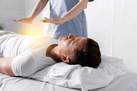 Foto de Vista parcial del sanador de pie cerca del hombre en la mesa de masaje y tomar las manos por encima de su cuerpo - Imagen libre de derechos