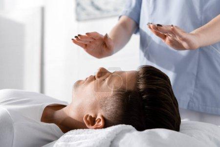Foto de Vista parcial del sanador de pie cerca del hombre en la almohada y torse las manos por encima de su cuerpo - Imagen libre de derechos