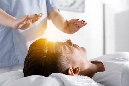 Photo pour Vue partielle du guérisseur debout près de l'homme sur l'oreiller et tenant les mains au-dessus de son corps - image libre de droit