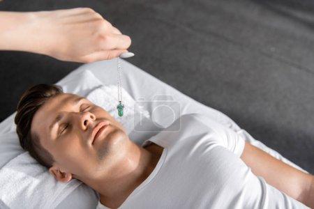 Photo pour Vue recadrée de l'hypnotiseur restant près de l'homme sur la table de massage et retenant la pierre verte - image libre de droit