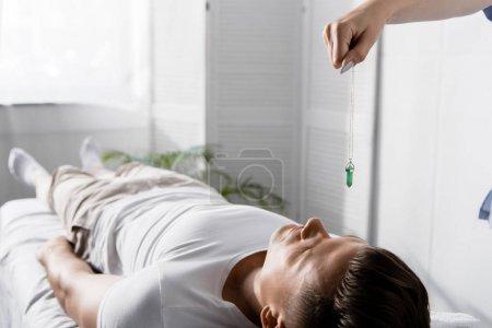 Foto de Vista recortada de hipnotizador de pie cerca del hombre en la mesa de masaje y la celebración de piedra verde - Imagen libre de derechos