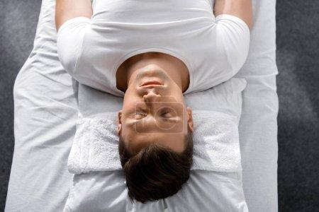 Photo pour Jeune homme se trouvant sur l'oreiller sur la table de massage avec les yeux fermés - image libre de droit