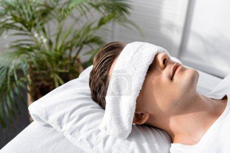 Photo pour Jeune homme avec la serviette sur des yeux se trouvant sur l'oreiller - image libre de droit
