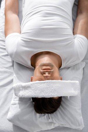 Photo pour Vue de dessus du jeune homme avec serviette sur les yeux couché sur l'oreiller - image libre de droit