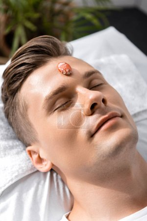 Photo for Smiling young man lying on pillow with closed eyes with stone on forehead - Royalty Free Image