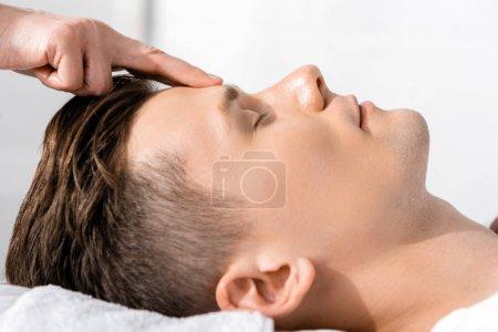 Photo pour Vue recadrée du masseur debout près de l'homme les yeux fermés et touchant son front - image libre de droit