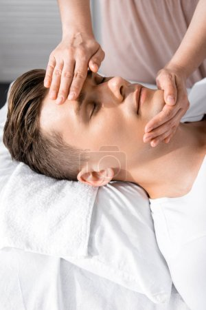 Photo for Cropped view of masseur standing near man with closed eyes and touching his face - Royalty Free Image