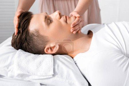 Photo pour Vue recadrée de masseur debout près de l'homme avec les yeux fermés et touchant son visage - image libre de droit