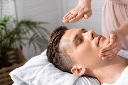 Photo pour Vue recadrée du guérisseur debout près de l'homme les yeux fermés et tenant les mains au-dessus de la tête - image libre de droit