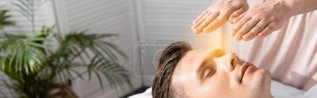 Foto de Disparo panorámico de sanador de pie cerca del hombre con los ojos cerrados y torse las manos por encima de la cabeza - Imagen libre de derechos