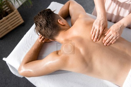 Photo for Cropped view of masseur and shirtless man lying on massage table - Royalty Free Image