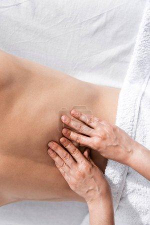 Photo pour Vue recadrée du masseur et de l'homme torse nu se trouvant sur la table de massage - image libre de droit