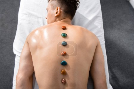 Photo pour Vue de dessus de l'homme torse nu couché sur la table de massage avec des pierres sur le dos - image libre de droit