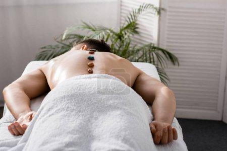 Photo pour Homme torse nu se trouvant sur la table de massage avec des pierres sur le dos - image libre de droit