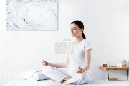 Photo pour Femme assise sur une table de massage en pose de lotus avec les yeux fermés - image libre de droit
