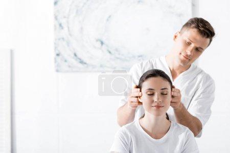 Photo pour Jeune femme s'asseyant avec les yeux fermés tandis que le masseur touchant ses oreilles - image libre de droit