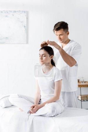 Photo pour Femme s'asseyant sur la table de massage avec les yeux fermés tandis que le guérisseur retenant des mains au-dessus de sa tête - image libre de droit