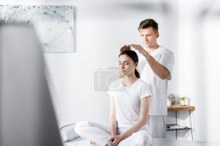 Photo for Woman sitting on massage table with closed eyes while healer holding hands above her head - Royalty Free Image