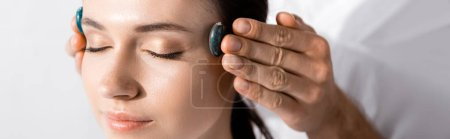 Photo for Panoramic shot of healer standing near woman with closed eyes and using stones - Royalty Free Image