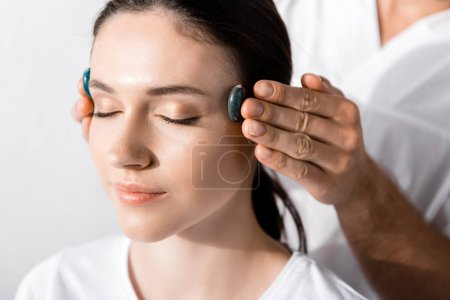 Photo for Cropped view of healer standing near woman with closed eyes and using stones - Royalty Free Image