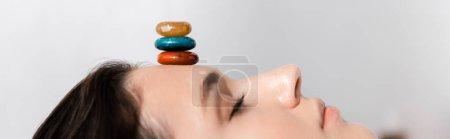 Photo pour Tir panoramique de femme se trouvant avec les yeux fermés avec des pierres colorées sur le front sur le gris - image libre de droit