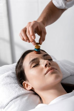 Photo pour Vue recadrée du guérisseur debout près d'une femme allongée sur un oreiller les yeux fermés et utilisant des pierres - image libre de droit