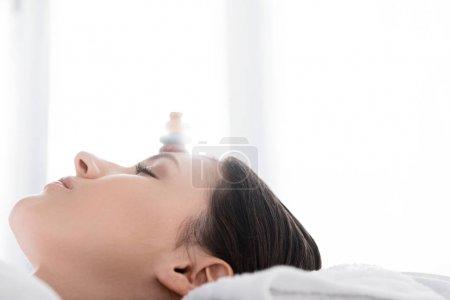 Photo pour Femme se trouvant avec les yeux fermés avec des pierres sur le front - image libre de droit