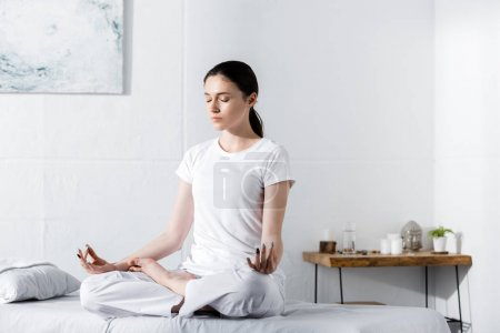 young woman sitting in lotus pose with closed eyes on massage table