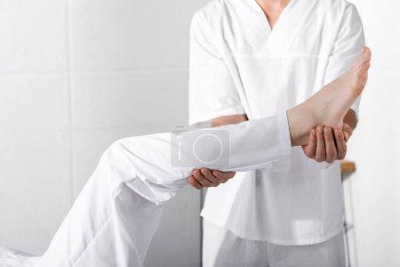 Photo pour Vue recadrée du masseur debout près de la femme et touchant sa jambe - image libre de droit