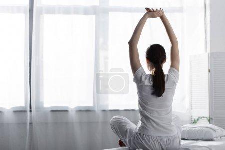 Photo pour Vue arrière de la femme avec la queue de cheval s'asseyant sur le lit et s'étirant dans la clinique - image libre de droit