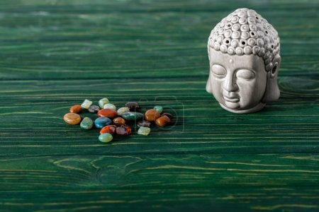 Photo pour Statuette bouddha et pierres semi-précieuses colorées sur surface en bois - image libre de droit