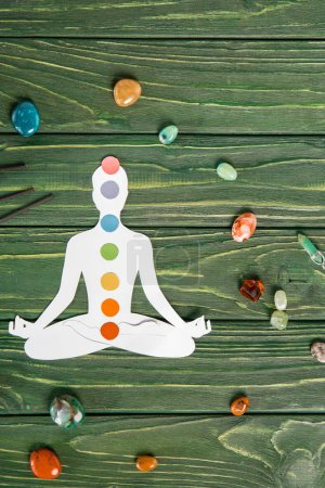 Photo for Top view of paper figure in form of person with chakras in lotus pose, aroma sticks and colorful stones on wooden surface - Royalty Free Image