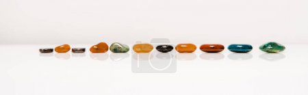 Photo pour Plan panoramique de pierres semi-précieuses colorées sur surface blanche isolée sur gris - image libre de droit